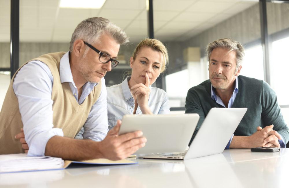 Team diskutiert am Laptop über Datensicherheit