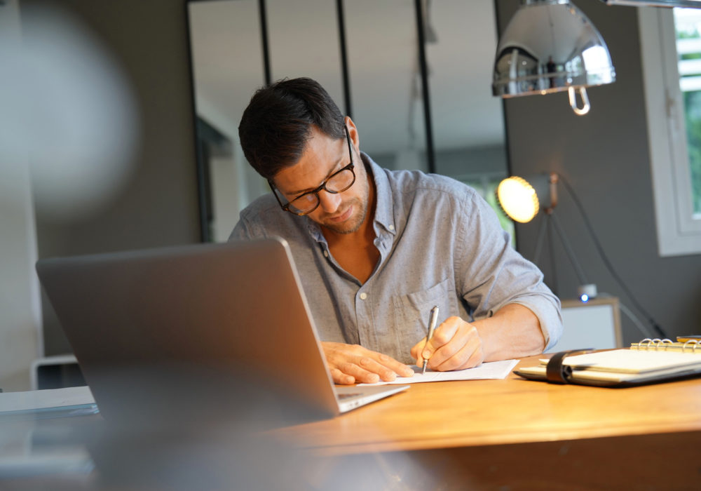 Mann prüft HR Kennzahlen des Personalcontrollings am Schreibtisch