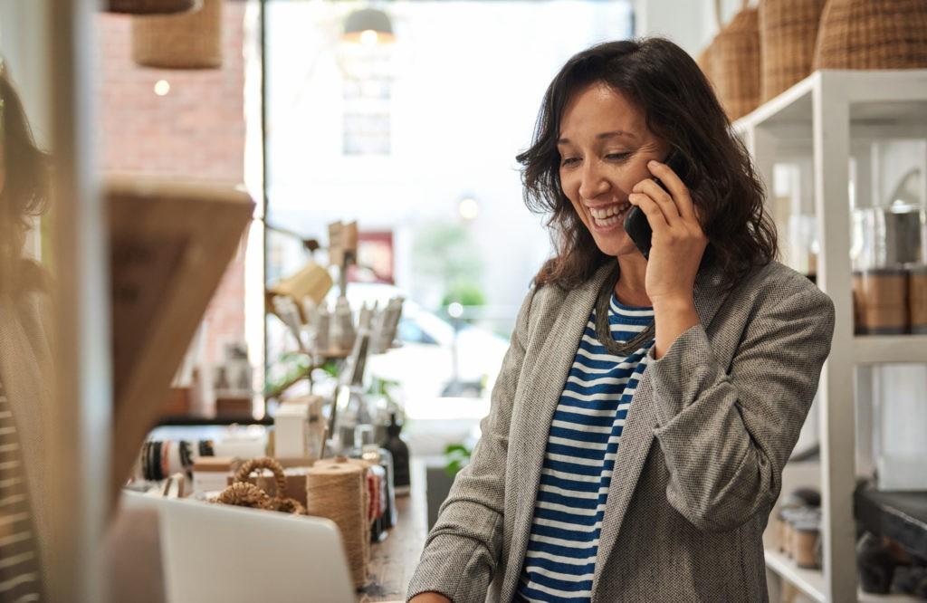 Frau stimmt ein Projekt am Handy von unterwegs ab