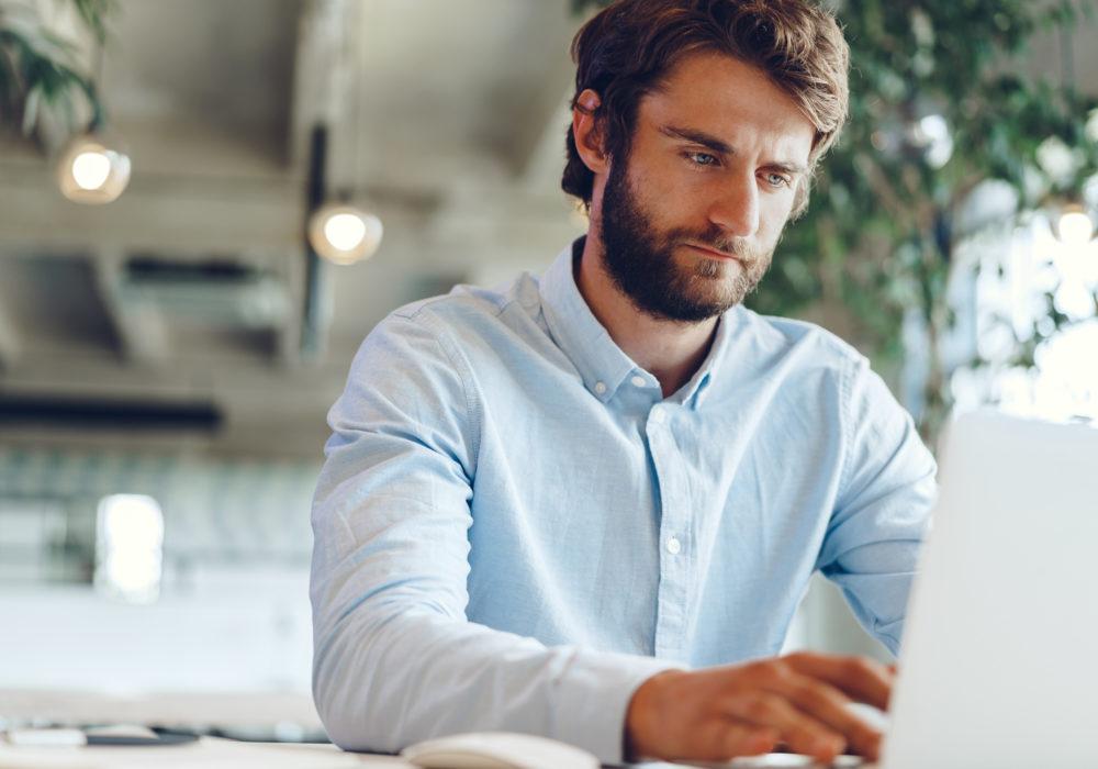 Mann arbeitet konzentriert mit Projektzeiterfassung am Desktop im Büro