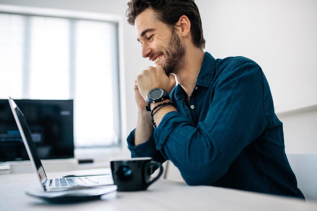 Mann am Schreibtisch freut sich über Single Sign-On