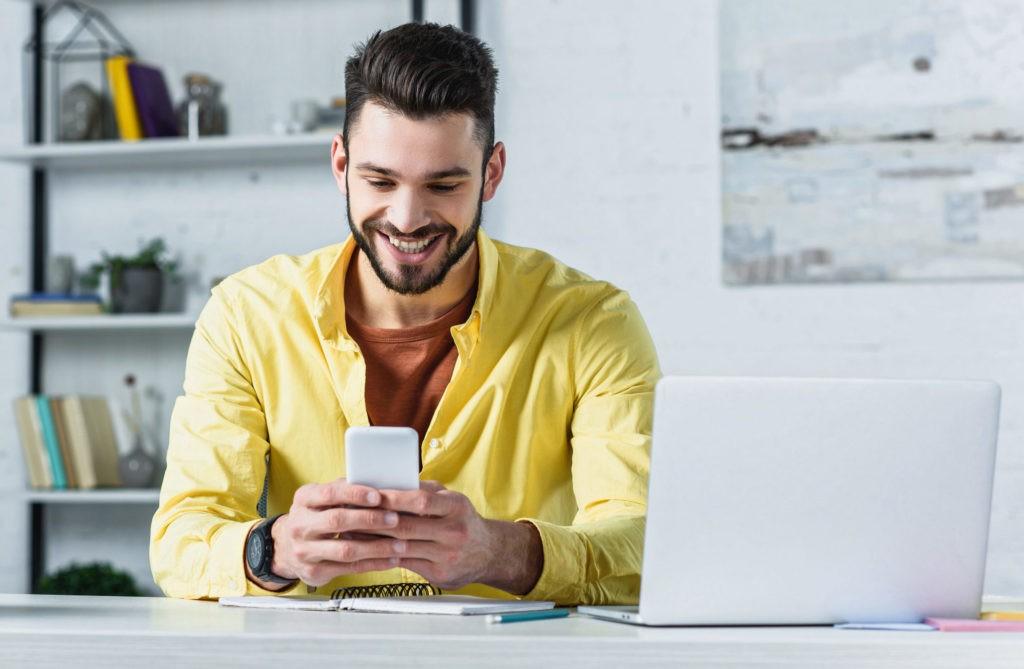 Mann prüft seine Zeitwirtschaft mit HR Software per Handy